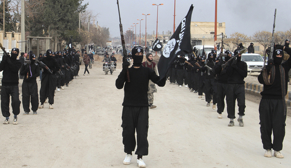 Fighters of al-Qaeda linked Islamic State of Iraq and the Levant carry their weapons during a parade at the Syrian town of Tel Abyad, near the border with Turkey January 2, 2014. Picture taken January 2, 2014. REUTERS/Yaser Al-Khodor
